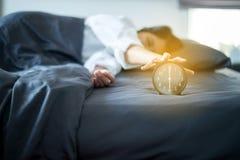 La femme asiatique déteste obtenir soumise à une contrainte réveillant tôt 6 heures le matin, réveil images libres de droits