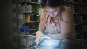 La femme asiatique d'adolescent lit et des contacts sur un dispositif de comprimé dans photos libres de droits