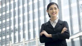 La femme asiatique d'affaires se tient avec la signalisation sûre à extérieur Photo libre de droits