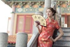 La femme asiatique dans le Chinois habillent tenir le couplet 'succès' (Chin image libre de droits