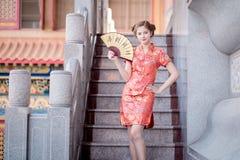 La femme asiatique dans le Chinois habillent tenir le couplet 'succès' (Chin Photographie stock libre de droits