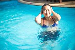 La femme asiatique dans un bikini bleu nage dans la piscine images stock