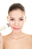 La femme asiatique de beauté mettant le maquillage rougissent sur le visage Photos libres de droits