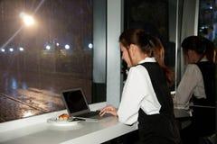 La femme asiatique de belles jeunes affaires travaille un ordinateur portable Images stock