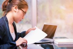 La femme asiatique de bureau jugeant de papier et regardant écrivent le papier, busine photographie stock libre de droits