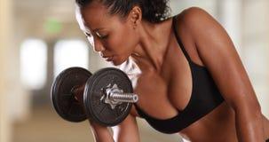 La femme asiatique de métis fort faisant le biceps se courbe au gymnase photos libres de droits