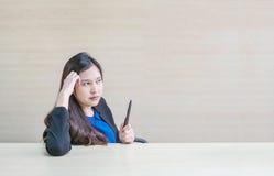 La femme asiatique de plan rapproché travaillant avec le visage de pensée et un stylo dans sa main sur le bureau et le mur en boi Image stock
