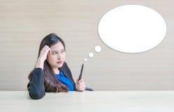 La femme asiatique de plan rapproché travaillant avec le visage et le crayon de pensée dans sa main sur le bureau en bois brouill Images libres de droits