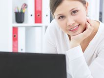 La femme asiatique de sourire d'affaires de jeunes travaille sur l'ordinateur portable à son bureau photos stock