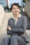 La femme asiatique de sourire d'affaires s'asseyent sur l'escalier Photos libres de droits