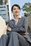La femme asiatique de sourire d'affaires s'asseyent sur l'escalier Images stock