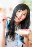 La femme asiatique de sourire mangeant une certaine fraise durcissent en café de boulangerie Photographie stock