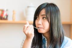 La femme asiatique de sourire mangeant une certaine fraise durcissent en café de boulangerie Photos stock