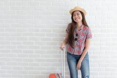 La femme asiatique disposent à voyager sur le mur de briques blanc, le mode de vie et le tourisme photos stock