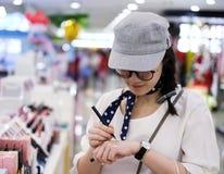 La femme asiatique examinent le stylo liquide d'eye-liner dans la boutique Image stock