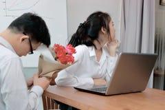 La femme asiatique fâchée refuse un bouquet des roses rouges de l'homme d'affaires Concept déçu d'amour Photographie stock libre de droits