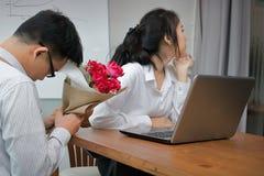 La femme asiatique fâchée refuse un bouquet des roses rouges de l'homme d'affaires dans le bureau Concept déçu d'amour Image libre de droits