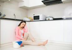 La femme asiatique a fatigué après les travaux domestiques se reposant dans la cuisine images stock