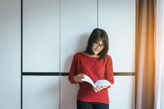 La femme asiatique lisant feelling debout de livre heureux et détendent image libre de droits