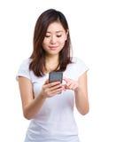 La femme asiatique a lu le message au téléphone portable photographie stock libre de droits