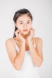 La femme asiatique massent son visage et appliquent le cosmétique crème Image libre de droits
