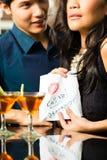 La femme asiatique séduit l'homme dans le restaurant Image stock