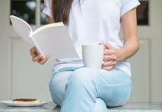 La femme asiatique s'asseyant sur la chaise de marbre devant la maison pour prennent le petit déjeuner et ont lu un livre pendant Photo stock