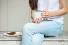La femme asiatique s'asseyant sur la chaise de marbre devant la maison pour prennent le petit déjeuner pendant le matin Photographie stock