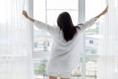 La femme asiatique se réveillant dans son lit a entièrement reposé et ouvre le curta images libres de droits