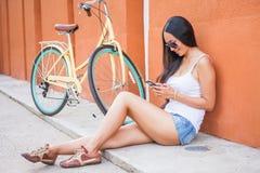 La femme asiatique sexy s'asseyant près du mur et le vintage vont à vélo Photos stock