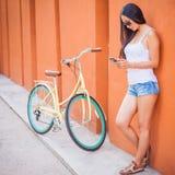 La femme asiatique sexy se tenant près du mur et le vintage vont à vélo Images stock