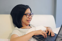 La femme asiatique soit heureuse son ordinateur portable sur un lit Photographie stock libre de droits
