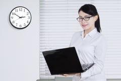 La femme asiatique tient l'ordinateur portable sur le lieu de travail Images libres de droits
