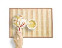 La femme asiatique versent le thé chaud d'une théière dans une tasse de thé sur le tapis en bois d'isolement sur le fond blanc Photos stock