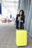 La femme asiatique vont voyage et à l'aide du téléphone portable avec la caisse de costume à a Photographie stock