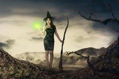 La femme assez asiatique de sorcière avec le balai magique émettent la lumière Image stock