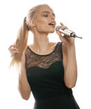 La femme assez blonde de jeunes chantant dans le microphone a isolé la robe noire haute étroite, fille de karaoke Photographie stock libre de droits