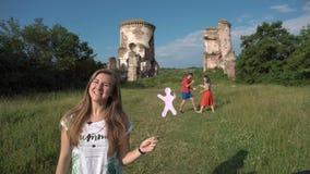 La femme assez blonde de jeunes parle à l'appareil-photo - garez avec le château à l'arrière-plan banque de vidéos