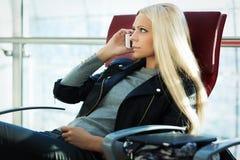 La femme assez blonde de jeunes parlent l'arport se reposant de téléphone portable Image stock