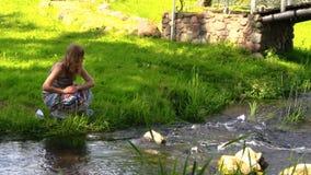 La femme assez enceinte a laissé le bateau de papier flotter sur l'eau de rivière banque de vidéos