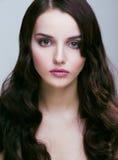 La femme assez jeune de brune avec la coiffure comme la coiffure mignonne de poupée ondule, maquillage fascinant Photo libre de droits