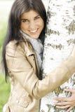La femme assez jeune met ses bras autour d'un arbre Images libres de droits