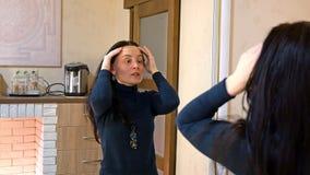 La femme assez longue de cheveux applique la crème sur son visage photos libres de droits