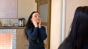 La femme assez longue de cheveux applique la crème sur son visage image stock