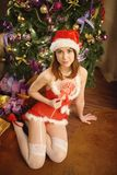 La femme assez sexy portant Santa Claus vêtx, se reposant sur une couverture chaude Image stock