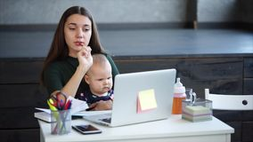 La femme assidue prend des notes dans le bureau avec son enfant banque de vidéos