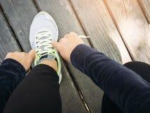 La femme attachant des dentelles folâtrent la formation courante de séance d'entraînement extérieure Photographie stock libre de droits