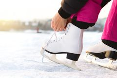 La femme attachant des patins de glace lace par un lac ou un étang Le laçage iceskates photo libre de droits