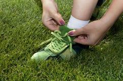 La femme attache des dentelles sur les chaussures vertes image libre de droits
