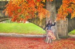 La femme atteignant l'automne a coloré des feuilles image libre de droits